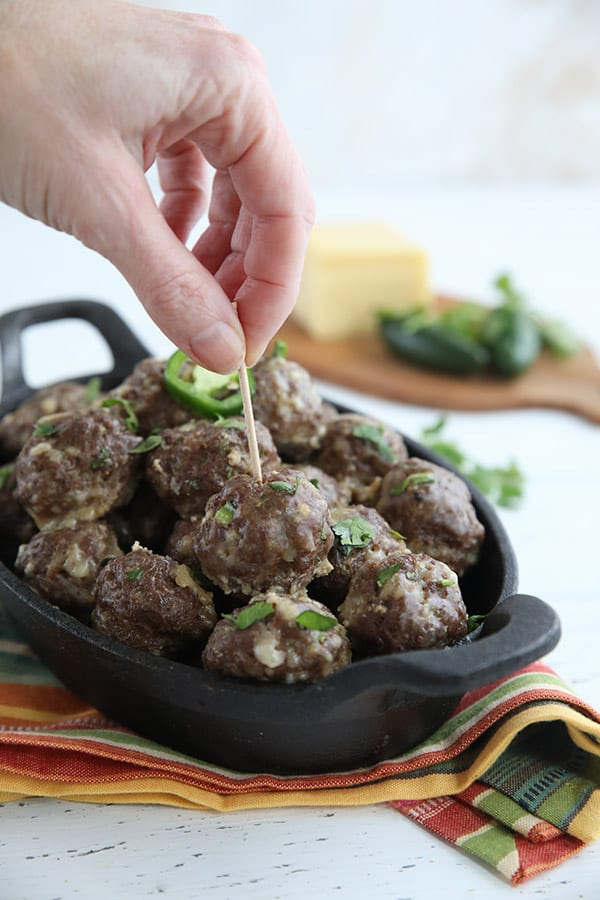 A hand reaching in with a toothpick to spear a keto meatball.