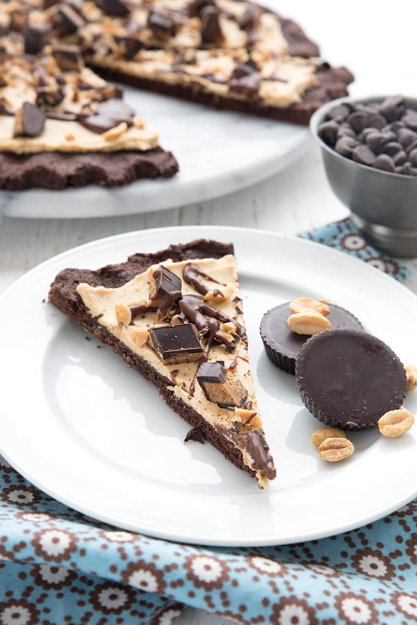 A slice of peanut butter cup dessert pizza on a white plate, with peanut butter cups and peanuts.