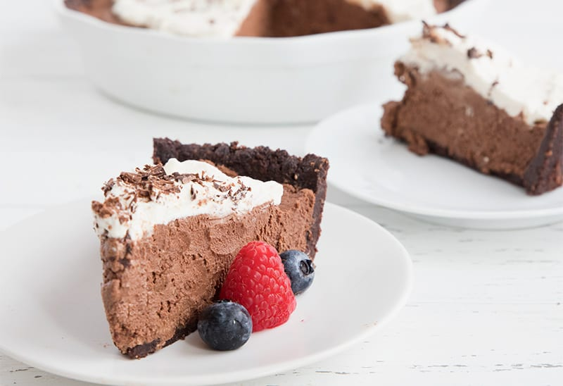 Two slices of sky high chocolate mousse pie on white plates on a white table.