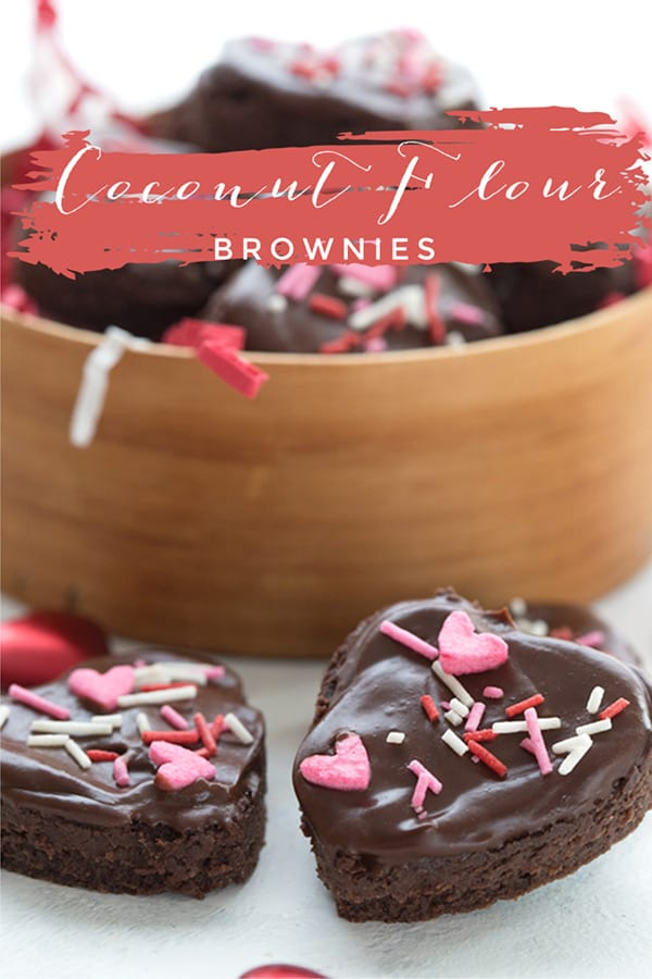 Keto coconut flour brownies with valentine's day sprinkles in front of a tin of more brownies.