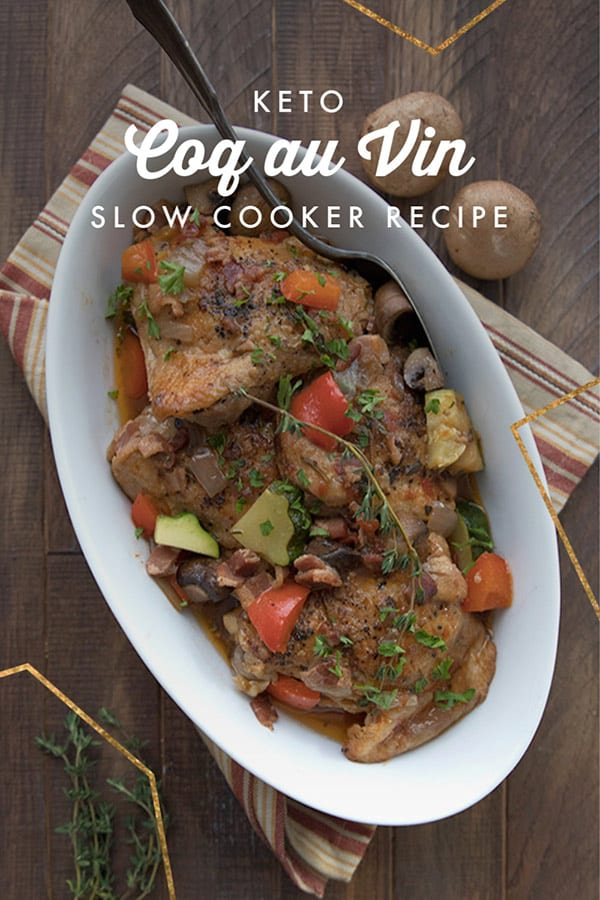 Top down photo of a white oval serving dish filled with coq au vin.