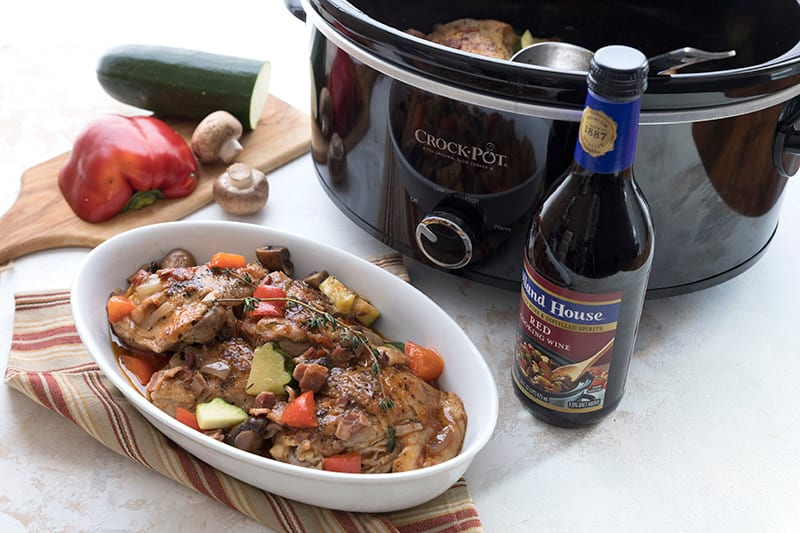 A crockpot on a white table with a serving dish of coq au vin in front of it.