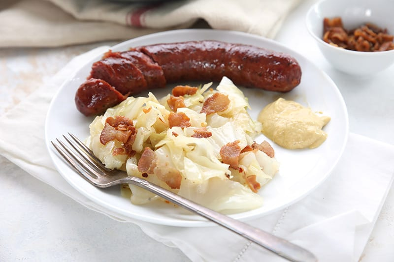 Fried cabbage on a white plate with mustard and kielbasa.