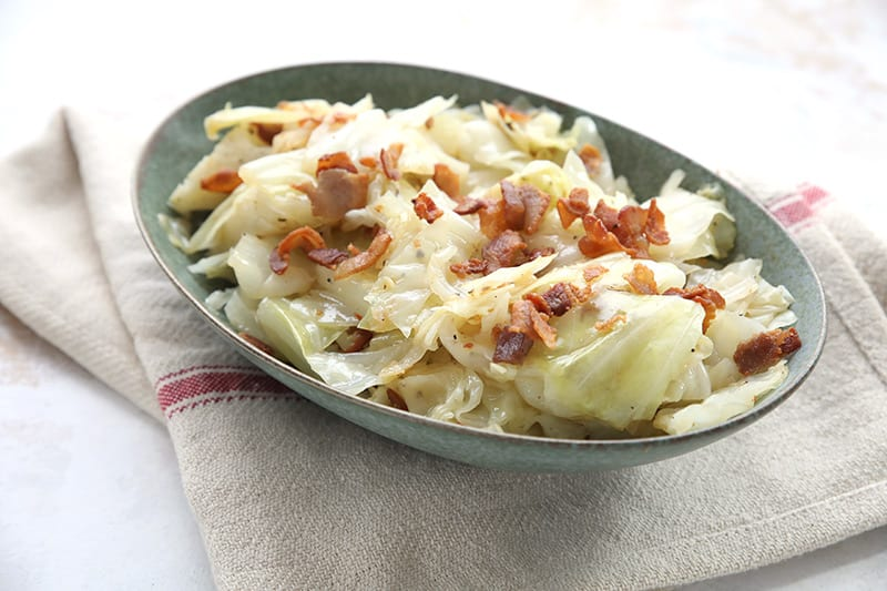 Instant Pot fried cabbage with bacon in a green serving bowl over a tan tea towel.