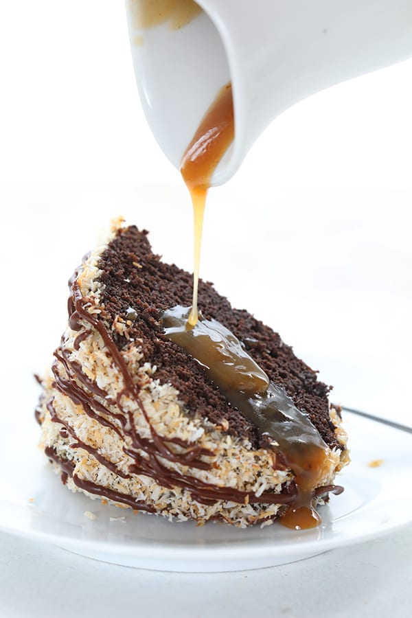 Keto caramel sauce being drizzled over a slice of low carb samoa cake.