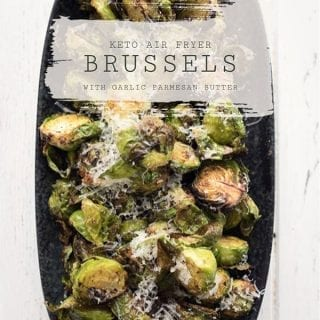 Top down photo of a black platter filled with air fryer Brussels sprouts on a white table.