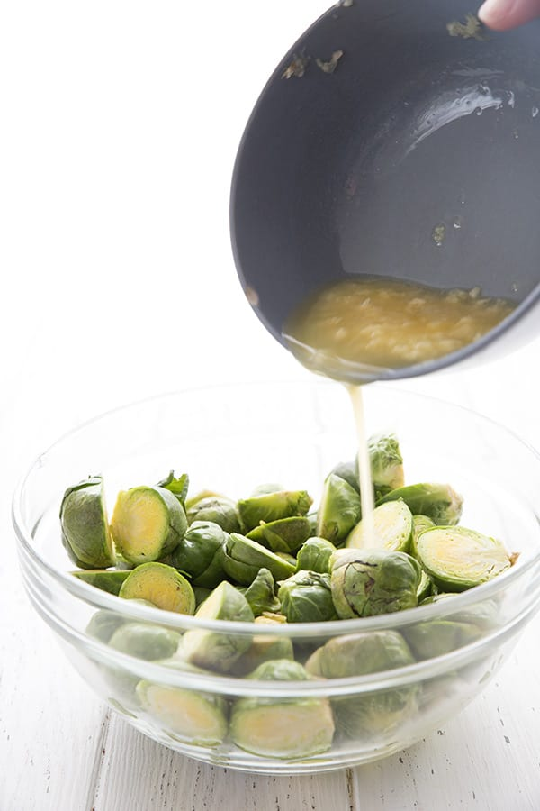 Garlic butter being poured over a bowl of raw Brussels sprouts.