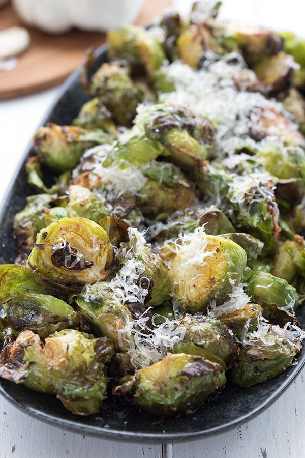 Close up shot of keto air fryer Brussels sprouts in a black serving dish.
