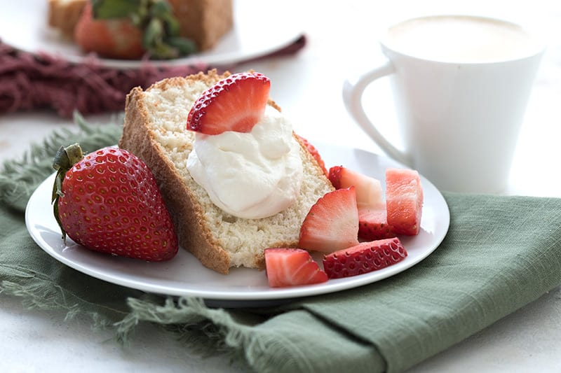 A slice of sugar-free and grain-free angel food cake with whipped cream and strawberries.