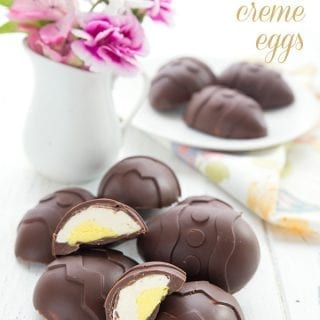 Keto easter creme eggs in a pile on a white table. A vase of flowers and a plate of chocolate eggs in the background.