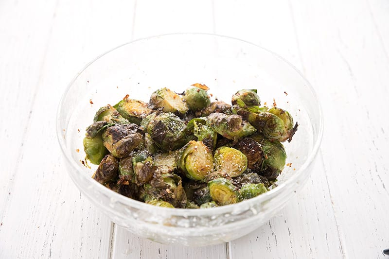 A glass bowl filled with air fried Brussels sprouts topped with parmesan and garlic.