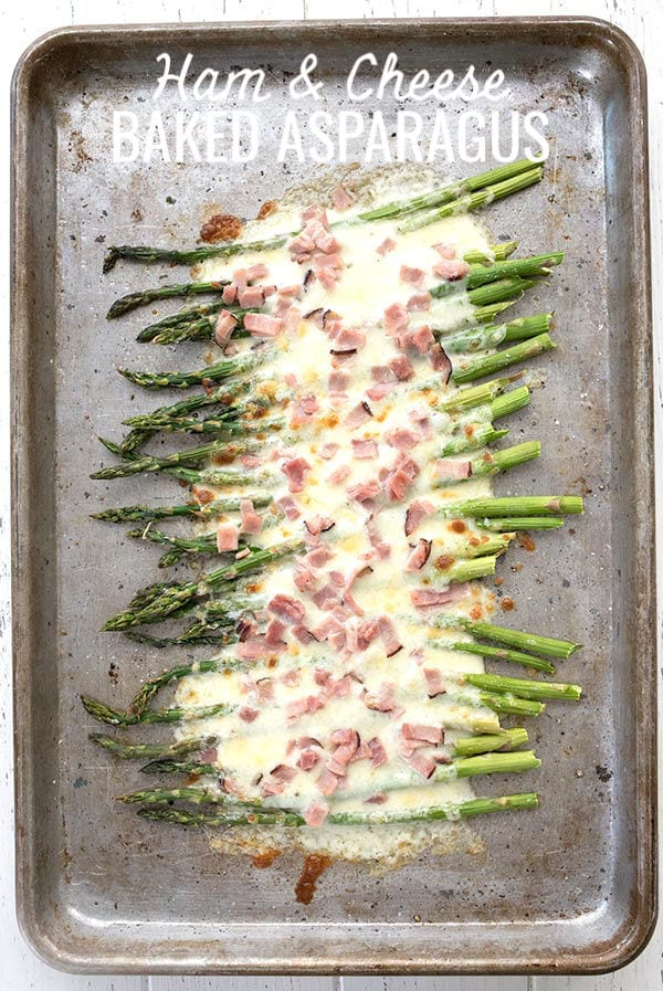 Cheesy baked asparagus on a metal baking pan, with ham on top.