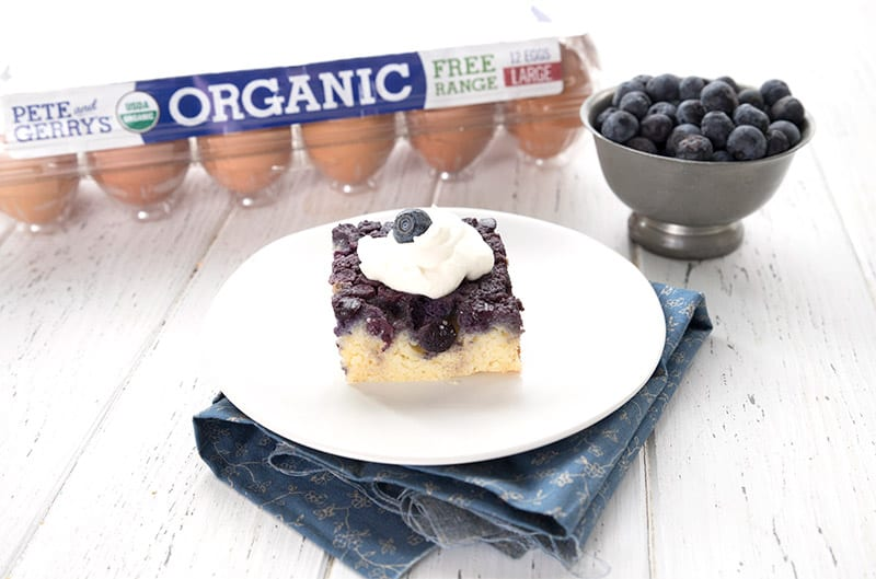 A single slice of keto blueberry upside down cake in front of a carton of eggs and a bowl of blueberries.