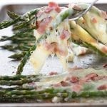 A fork pulling cheesy asparagus up from a baking sheet