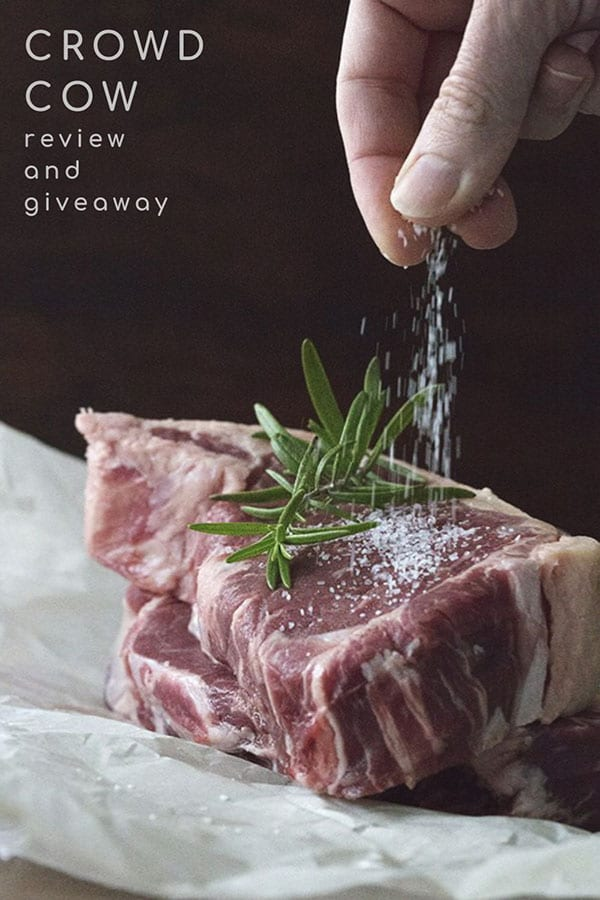 Salt being sprinkled on two grassfed steaks