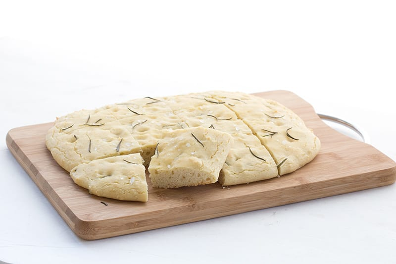 A large cutting board with a loaf of keto focaccia cut into squares.