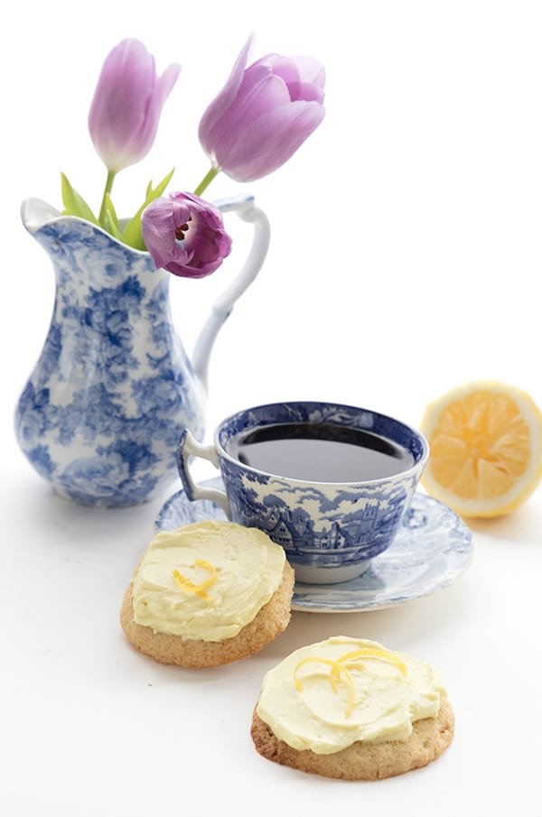 Two lemon sugar cookies with a cup of tea in a blue pattered cup. A vase with tulips in the background.