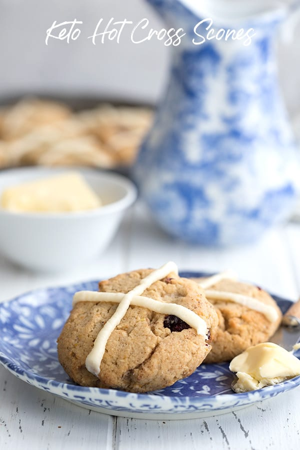 Hot cross scones on a blue patterned plate with a smear of butter.
