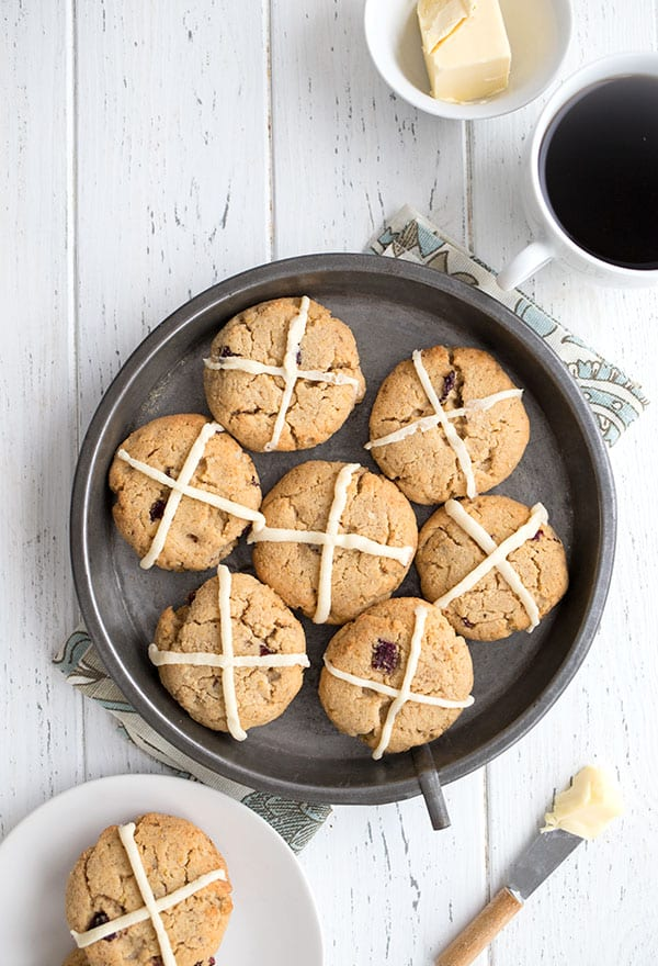 Top down photo of keto hot cross scones in a pan on a white table, with a cup of coffee and butter.