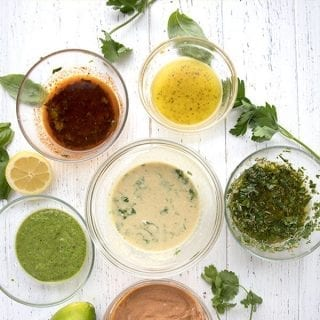 Titled image of 6 keto chicken marinades in glass bowls on a white table.