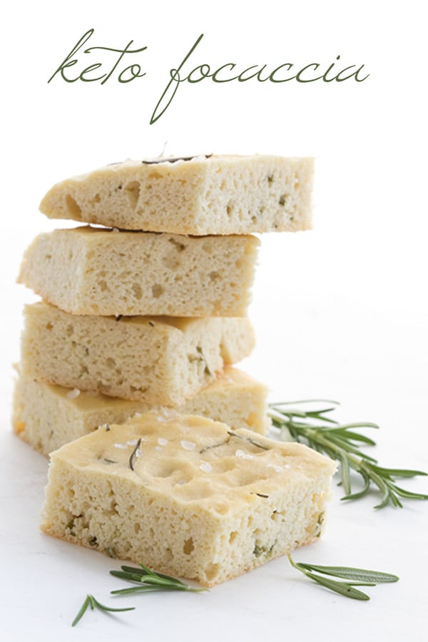 Keto focaccia bread in a stack with sprigs of rosemary around it.