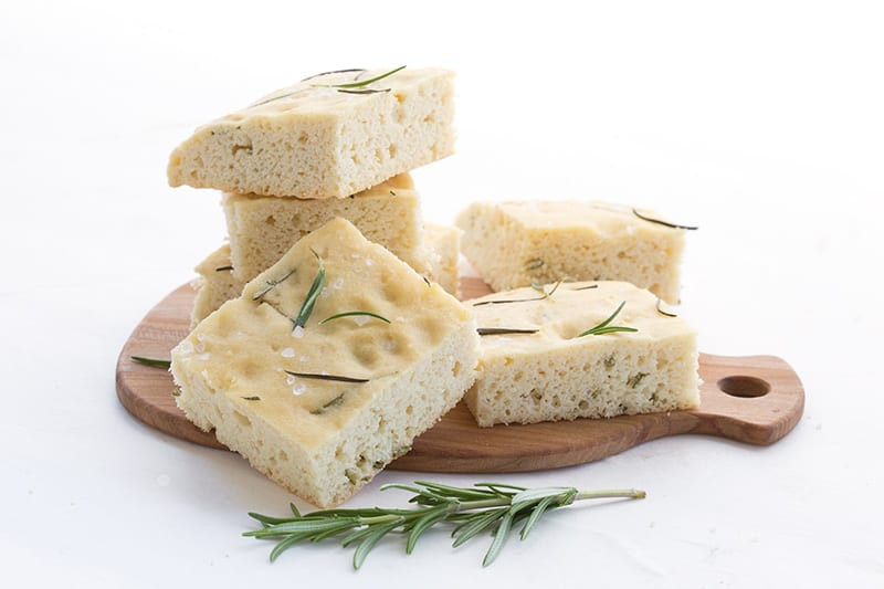 Slices of keto focaccia on a small wooden cutting board. A sprig of rosemary in front.