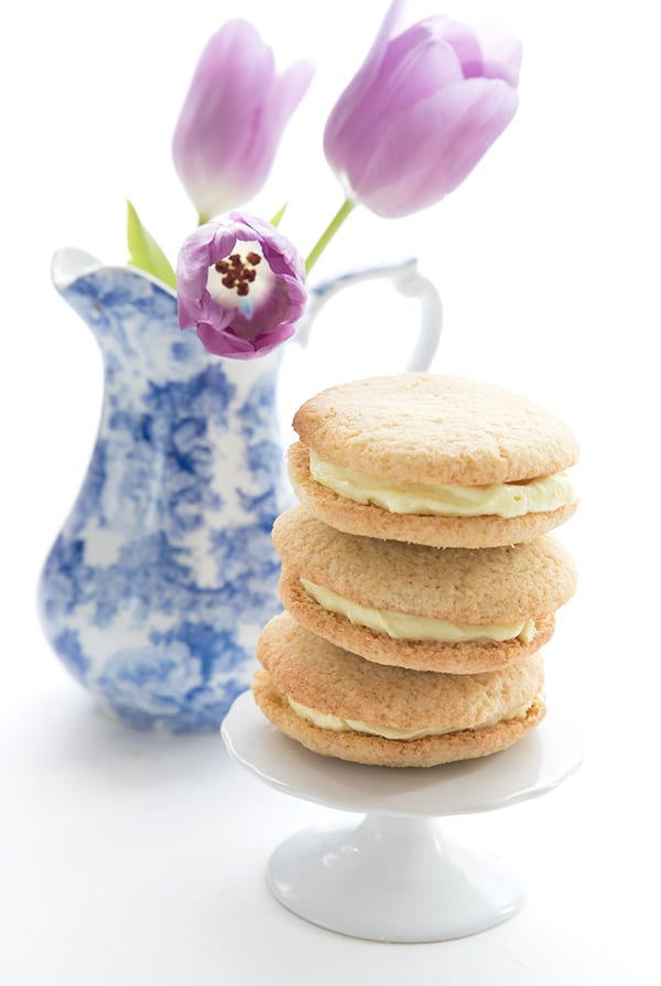 Keto lemon sugar cookies in a stack on a white plate with a blue vase of flowers in the background.