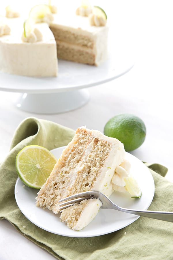 A slice of margarita cake on a white plate over a green napkin, with limes and the rest of the cake in the background.