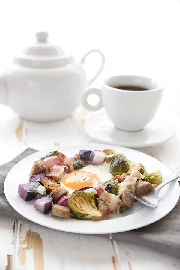 A serving of sheet pan breakfast on a white plate with coffee in the background