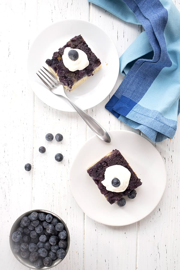 Top down photo of slices of blueberry upside down cake on a white table, with a blue napkin and a bowl of berries.