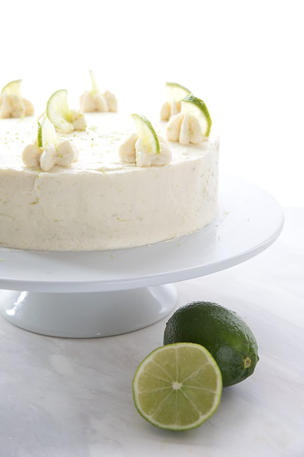 The whole keto margarita cake on a cake platter with two limes in front.