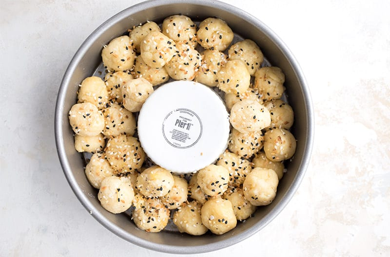 Top down photo of raw fathead dough balls in a round pan with everything bagel seasoning.