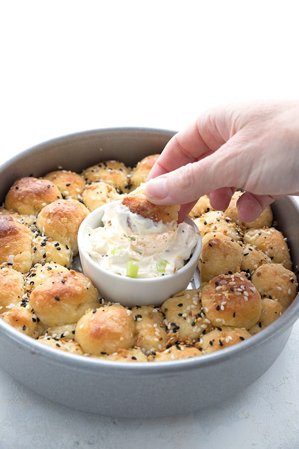 A hand dipping a piece of keto pull apart bread into cream cheese dip in the center of the pan.