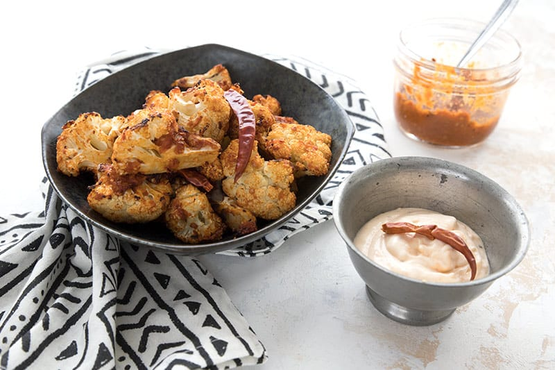 A black bowl filled with air fryer roasted cauliflower with a jar of homemade harissa and a small bowl of aioli