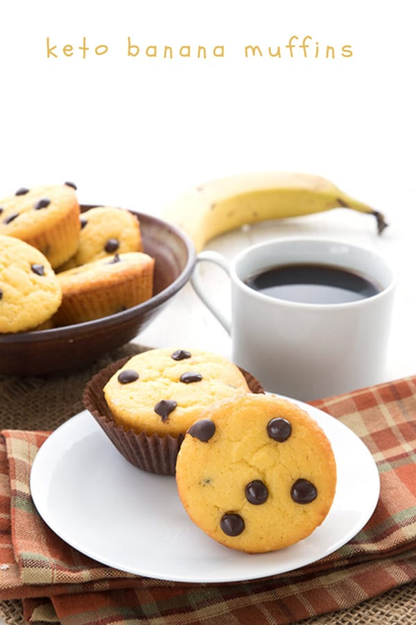 Two keto banana chocolate chip muffins on a white plate over a plaid napkin. A basket of muffins, a cup of coffee, and a banana in the background.