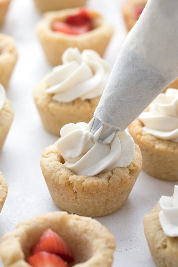 A frosting piping bag is piping whipped cream into keto cookie cups filled with strawberries