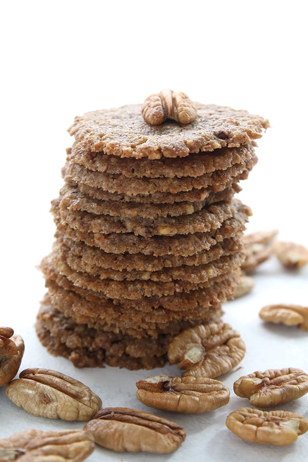 A tall stack of keto pecan lace cookies with pecans all around.