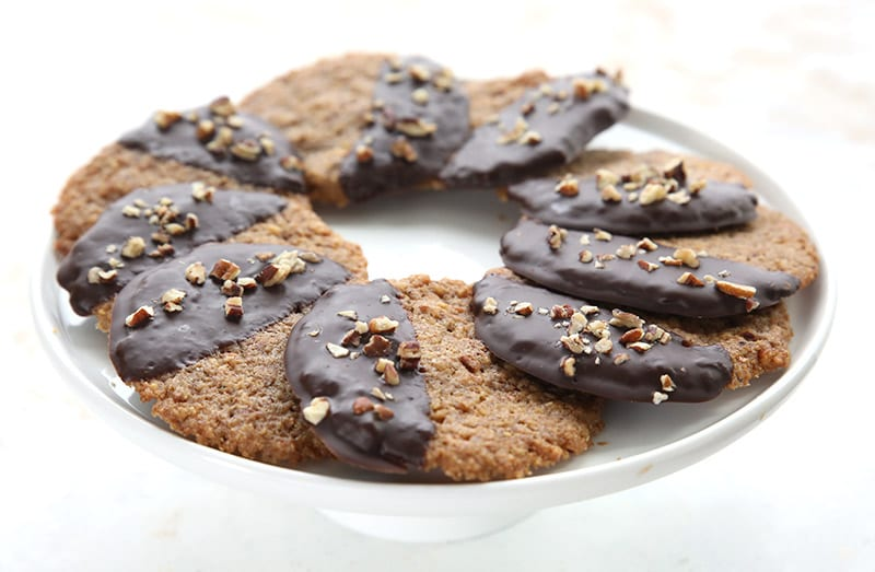 A round cake plate full of chocolate covered keto pecan cookies