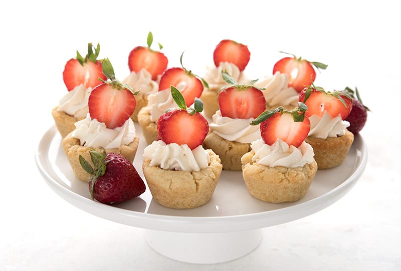 A white cake stand with keto sugar cookie cups filled with whipped cream and strawberries