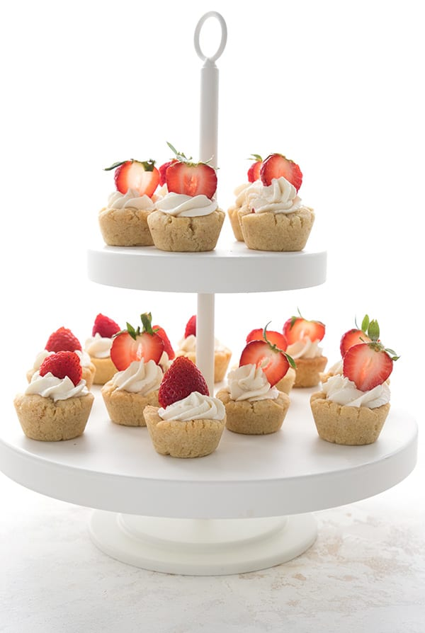 A tiered cake stand filled with strawberry shortcake cookie cups