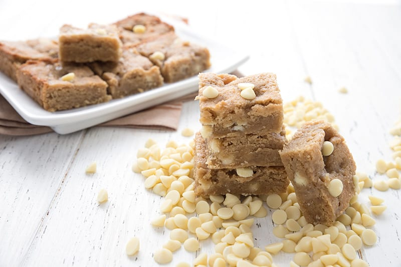 White chocolate blondies in a pile of white chocolate chips, with a plate of blondies in behind.