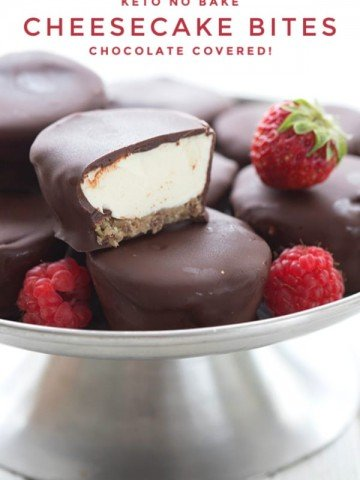 Titled image of keto cheesecake bites, with a close up of one bite cut open to show the filling inside, on top of other cheesecake bites on a metal platter
