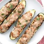 Top down photo of stuffed zucchini boats on a white plate over a red checked napkin