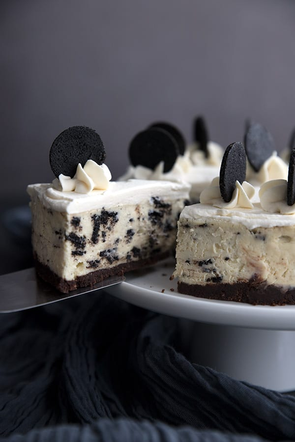 A slice of keto cookies and cream cheesecake being lifted out of the rest of the cake