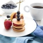 Two mini pancake skewers on a white plate with a strawberry. A cup of coffee and a bowl of blueberries in the background.