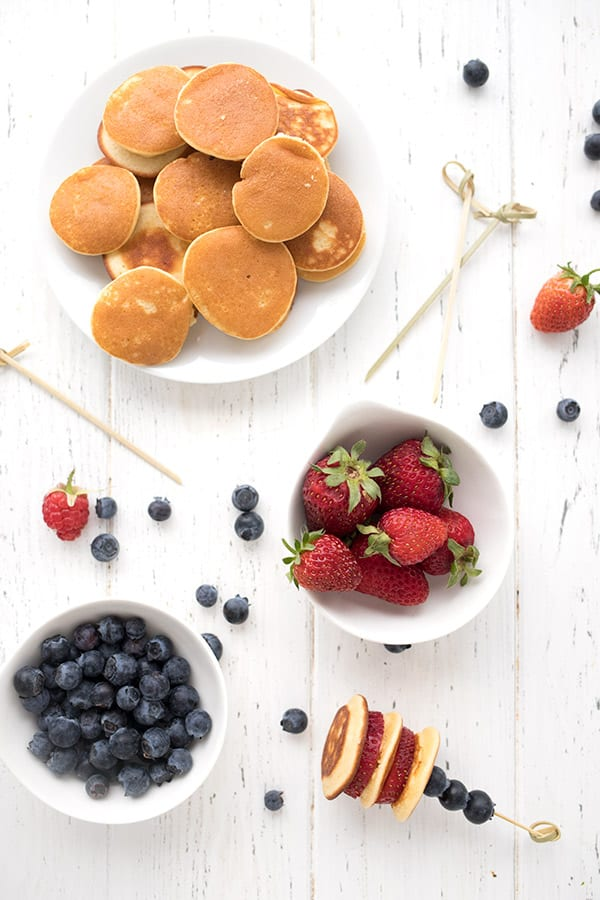 Top down photo of keto pancake skewer ingredients, with a plate of mini pancakes, and bowls of blueberries and strawberries.
