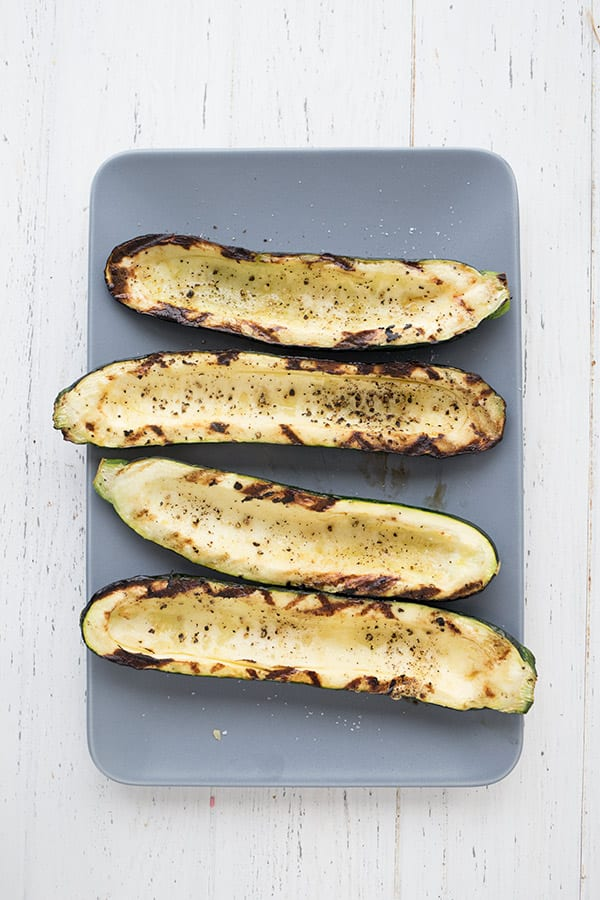 Top down photo of grilled zucchini boats, unfilled, on a blue rectangular plate