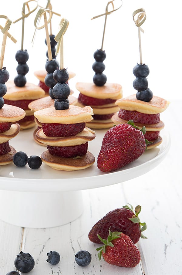 A cake plate full of mini pancake skewers on a white wooden table.