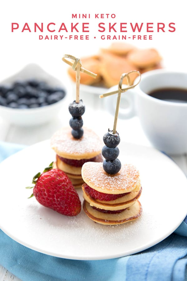 Titled image of keto mini pancake skewers on a white plate over a blue napkin. A cup of coffee, a bowl of blueberries and a plate of mini pancakes in the background.