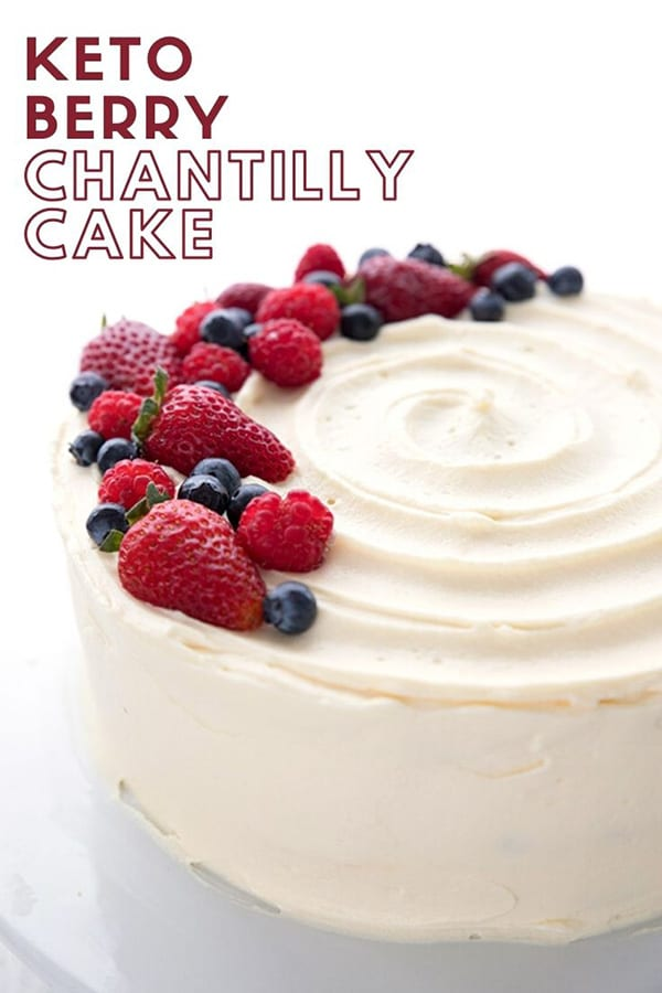 Titled Image of a Keto Chantilly Cake on a white cake platter, topped with fresh berries